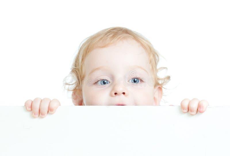 Enfant mignon bouclé retenant le drapeau de publicité blanc image libre de droits