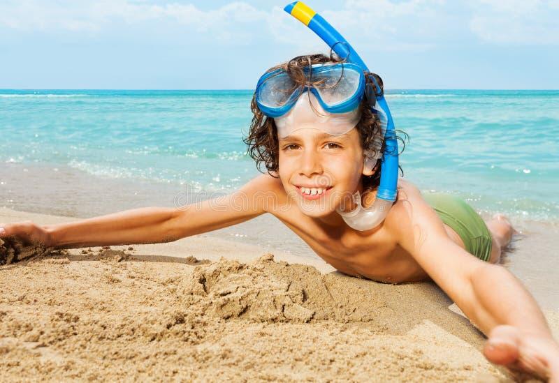 Enfant mignon dans le masque de scaphandre s'étendant sur la plage sablonneuse images libres de droits