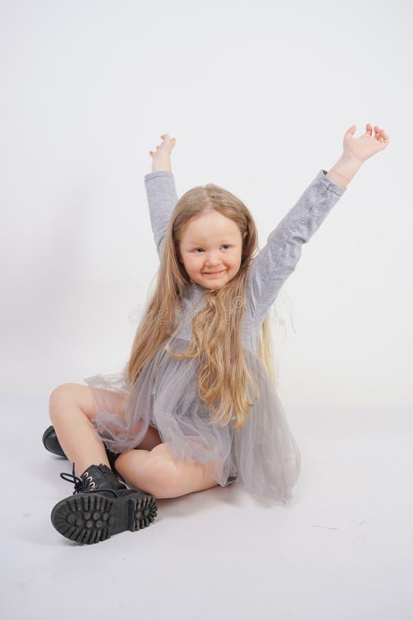 Enfant mignon de fille avec de longs cheveux blonds se reposant sur le plancher et les bâillements gentiment, étirant ses mains images stock