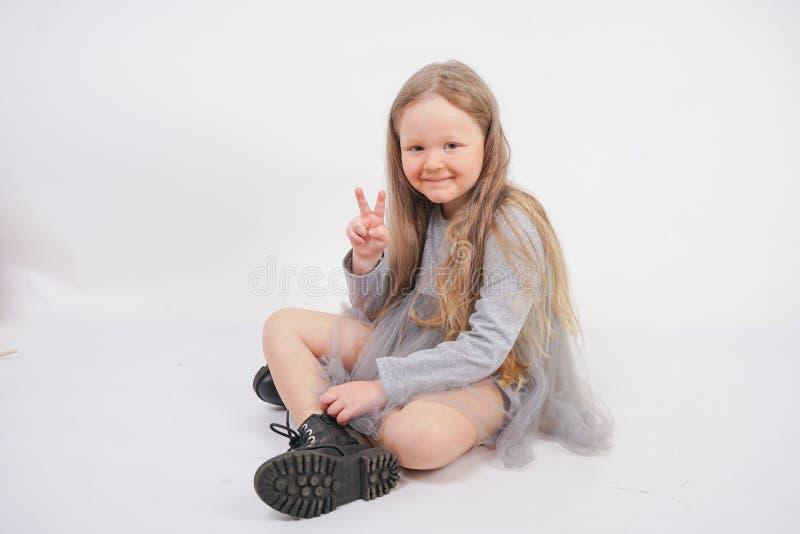 Enfant mignon de fille avec de longs cheveux blonds se reposant sur le plancher et les bâillements gentiment, étirant ses mains image stock