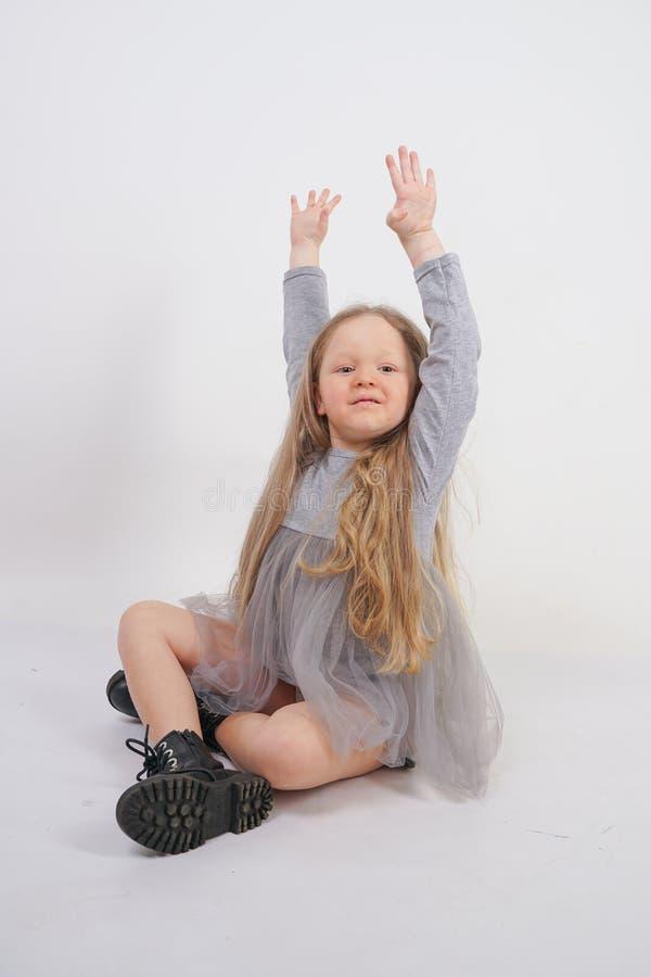 Enfant mignon de fille avec de longs cheveux blonds se reposant sur le plancher et les bâillements gentiment, étirant ses mains photos stock