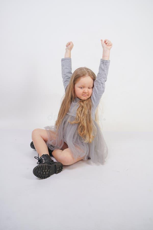 Enfant mignon de fille avec de longs cheveux blonds se reposant sur le plancher et les bâillements gentiment, étirant ses mains photographie stock libre de droits