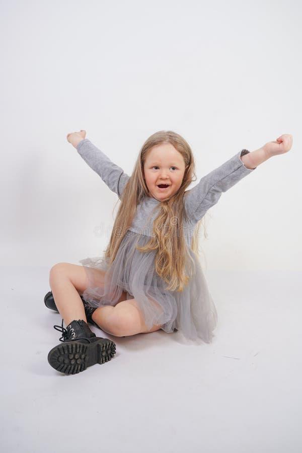 Enfant mignon de fille avec de longs cheveux blonds se reposant sur le plancher et les bâillements gentiment, étirant ses mains photo stock