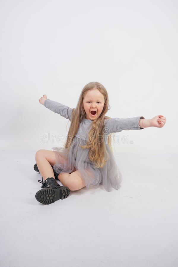 Enfant mignon de fille avec de longs cheveux blonds se reposant sur le plancher et les bâillements gentiment, étirant ses mains photographie stock