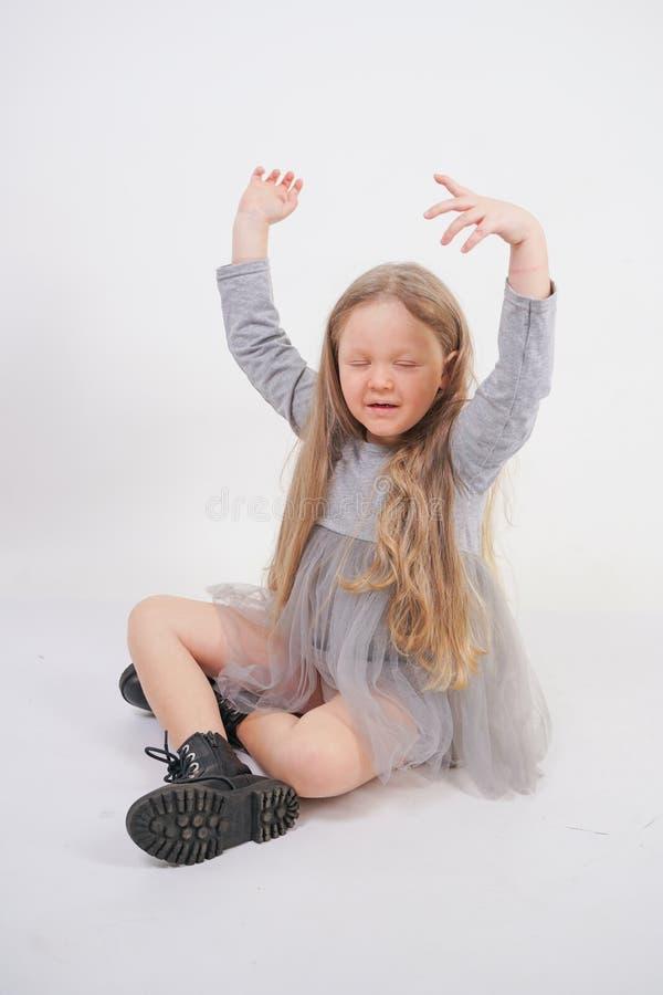 Enfant mignon de fille avec de longs cheveux blonds se reposant sur le plancher et les bâillements gentiment, étirant ses mains photo libre de droits