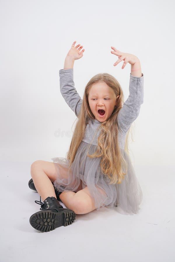 Enfant mignon de fille avec de longs cheveux blonds se reposant sur le plancher et les bâillements gentiment, étirant ses mains images libres de droits