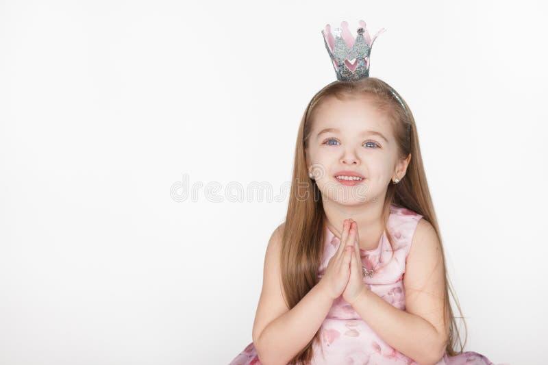 Enfant mignon de petite fille priant et recherchant photo libre de droits