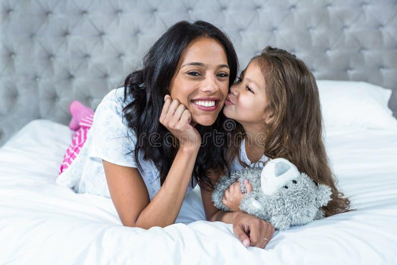 Enfant mignon embrassant sa mère sur le lit photographie stock