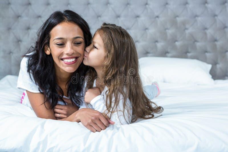 Enfant mignon embrassant sa mère sur le lit images libres de droits