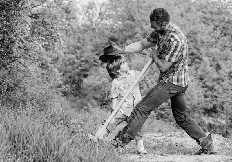 Enfant mignon en nature ayant le papa de cowboy d'amusement Trouvez les tr?sors Peu gar?on et p?re avec la pelle recherchant des  photo libre de droits