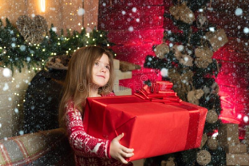 Enfant mignon et joyeux qui ouvre un cadeau de Noël La petite fille présente son cadeau avec un visage reconnaissant La vraie joi photos libres de droits