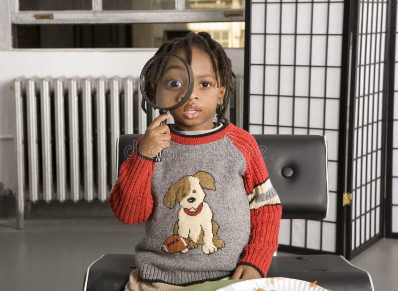 Enfant mignon jouant avec une loupe photo stock