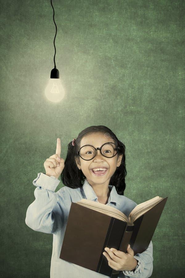 Enfant mignon obtenant l'inspiration avec l'ampoule photo libre de droits