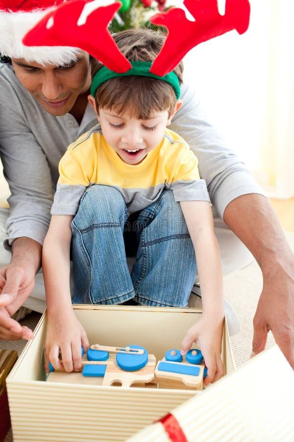 Enfant mignon ouvrant un cadeau de Noël images libres de droits