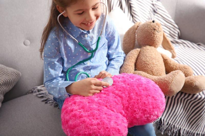 Enfant mignon s'imaginant docteur tout en jouant avec le stéthoscope sur le sofa images libres de droits