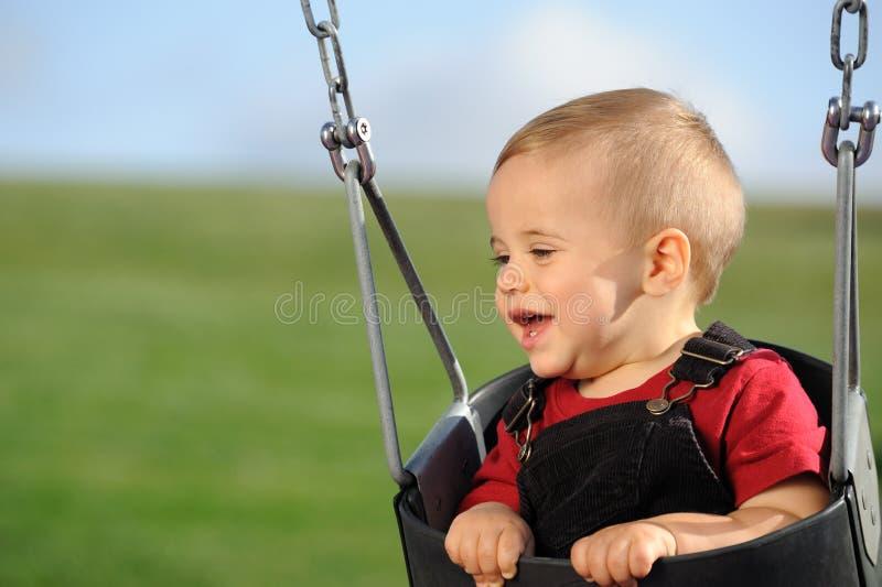 Enfant mignon sur l'oscillation de cour de jeu image stock