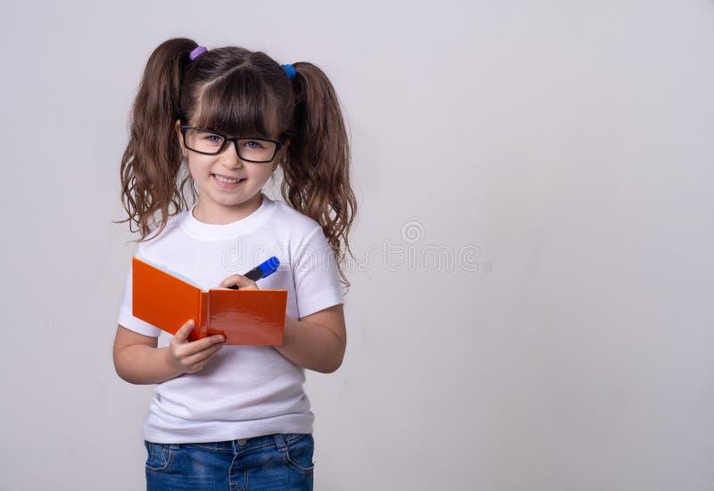 Enfant mignon surpris dans les lunettes, écrivant dans un carnet avec un crayon, gardant la bouche large ouverte Quatre ou cinq a photographie stock