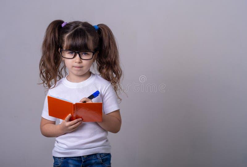 Enfant mignon surpris dans les lunettes, écrivant dans un carnet avec un crayon, gardant la bouche large ouverte Quatre ou cinq a photos libres de droits