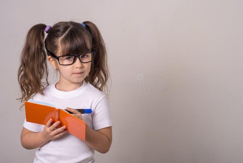 Enfant mignon surpris dans les lunettes, écrivant dans un carnet avec un crayon, gardant la bouche large ouverte Quatre ou cinq a image libre de droits