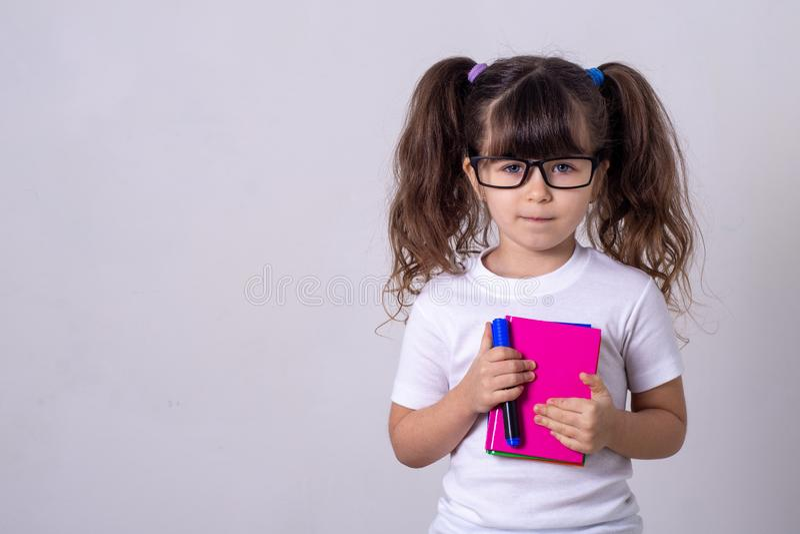Enfant mignon surpris dans les lunettes, écrivant dans un carnet avec un crayon, gardant la bouche large ouverte Quatre ou cinq a images stock