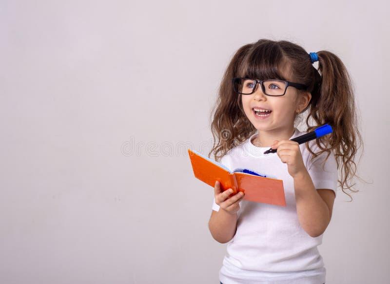 Enfant mignon surpris dans les lunettes, écrivant dans un carnet avec un crayon, gardant la bouche large ouverte Quatre ou cinq a photo stock