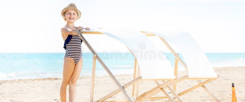 Enfant moderne de sourire dans le maillot de bain sur la plage près de la chaise de plage photos libres de droits