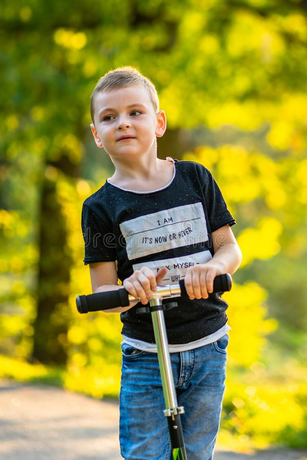 Enfant montant un scooter en parc à l'arrière-plan coloré d'Autum images stock