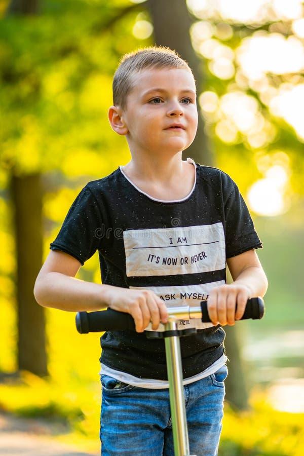 Enfant montant un scooter en parc à l'arrière-plan coloré d'Autum image libre de droits