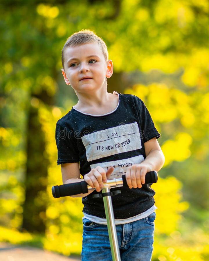 Enfant montant un scooter en parc à l'arrière-plan coloré d'Autum photos stock
