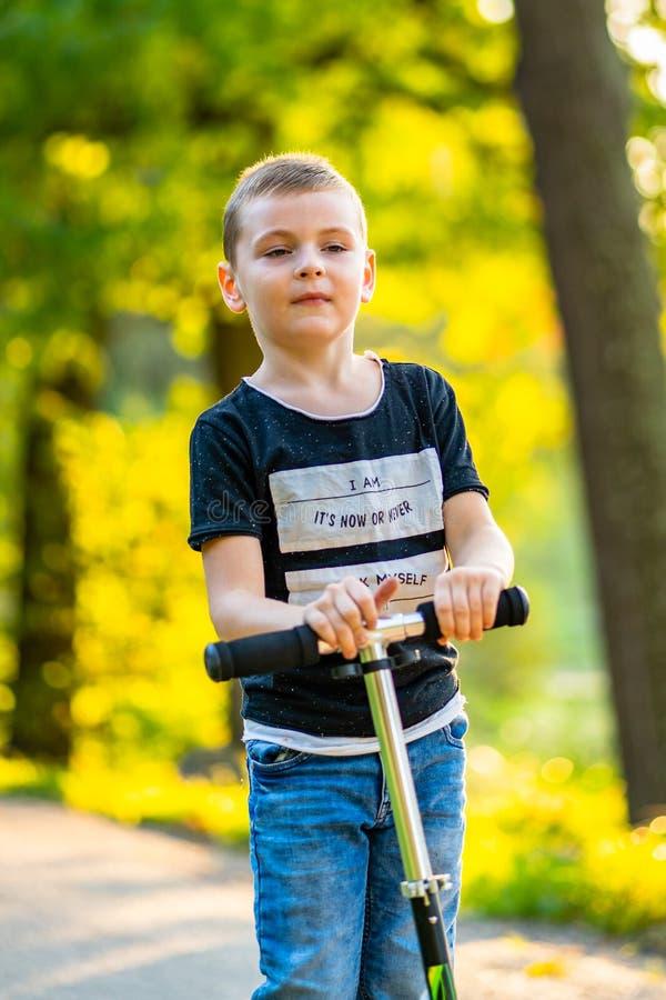 Enfant montant un scooter en parc à l'arrière-plan coloré d'Autum photographie stock