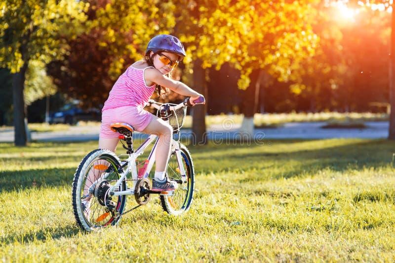 Enfant montant une bicyclette L'enfant dans le casque sur le vélo images libres de droits