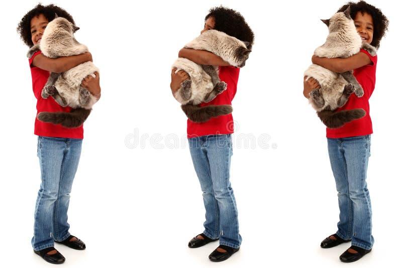 Enfant noir adorable retenant un grand chat image libre de droits