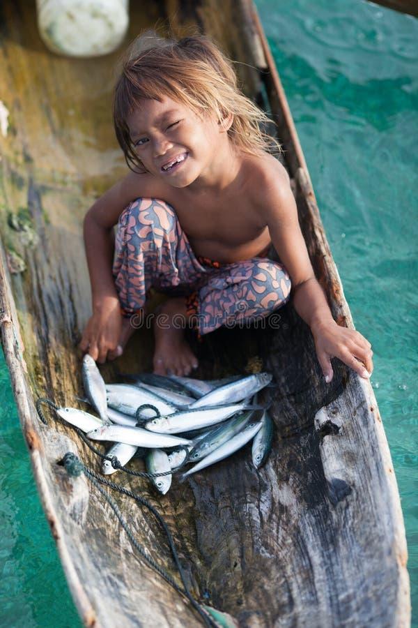Enfant non identifié sur les canoës avec des poissons à l'île de Mabul photos libres de droits
