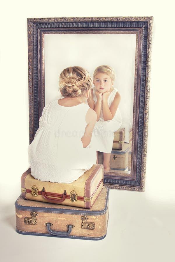Enfant ou jeune fille regardant fixement elle-même dans un miroir image stock