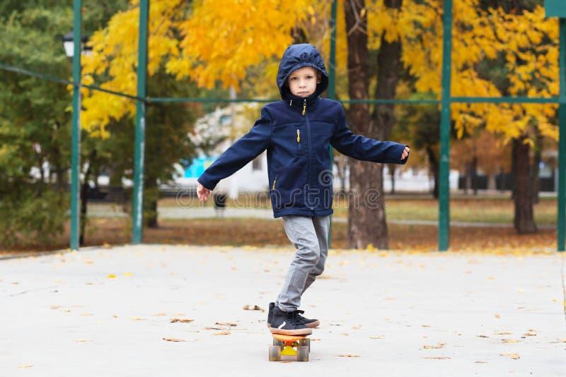 Enfant patinant en parc d'automne Style de ville Gosses urbains Prairie d'enfant images stock