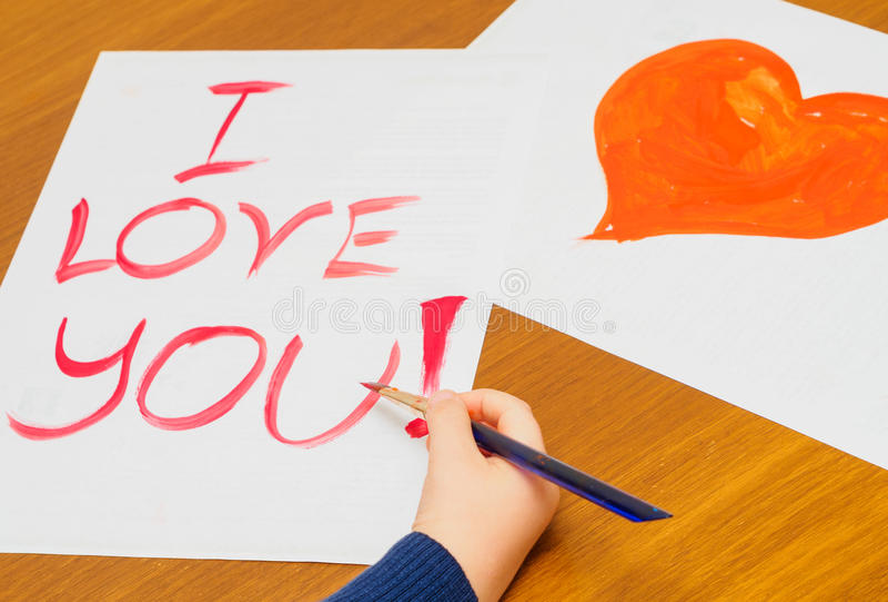 Enfant peignant je t'aime sur le papier photos stock