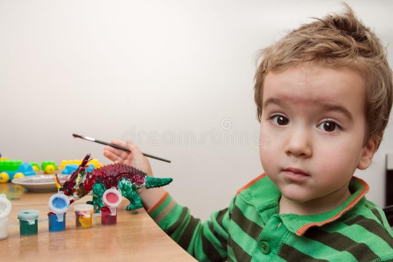 Enfant peignant un dinosaure en céramique de modèle de poterie sur le bureau photo stock