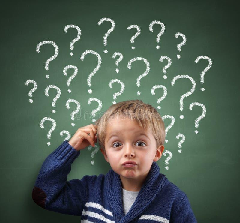 Enfant pensant avec le point d'interrogation sur le tableau noir photo libre de droits