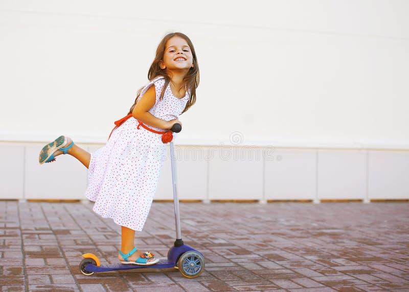 Enfant positif heureux dans la robe sur le scooter dans la ville photographie stock