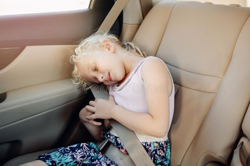 Enfant préscolaire de fille s'asseyant dans le siège de voiture Enfant de sommeil dans l'automobile photographie stock