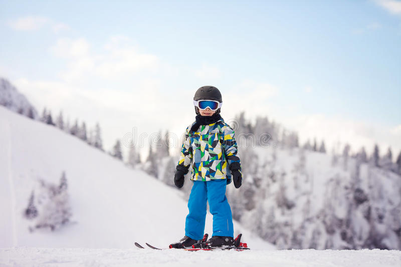 Enfant préscolaire mignon, garçon, skiant heureusement dans la station de sports d'hiver autrichienne photo libre de droits