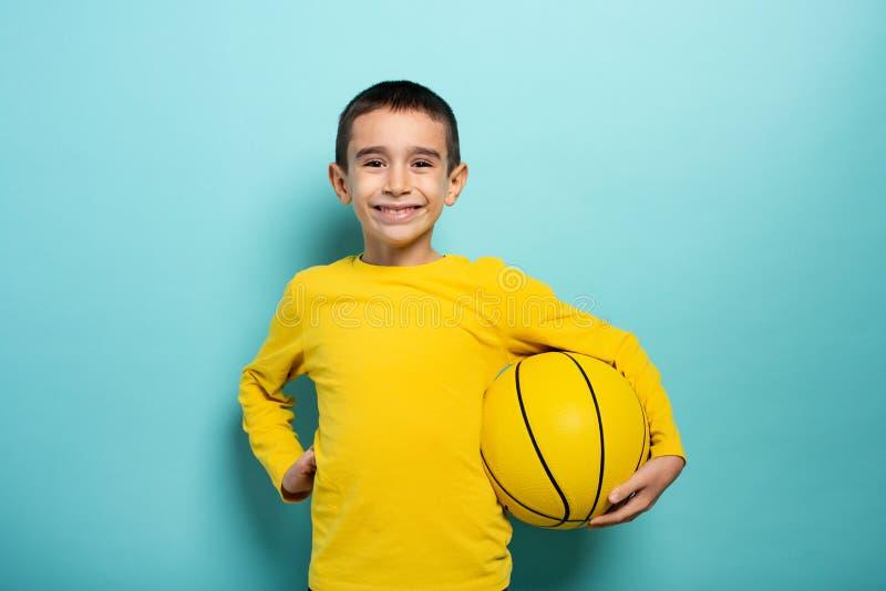 Enfant prêt à jouer au basket-ball Arrière-plan cyan images libres de droits
