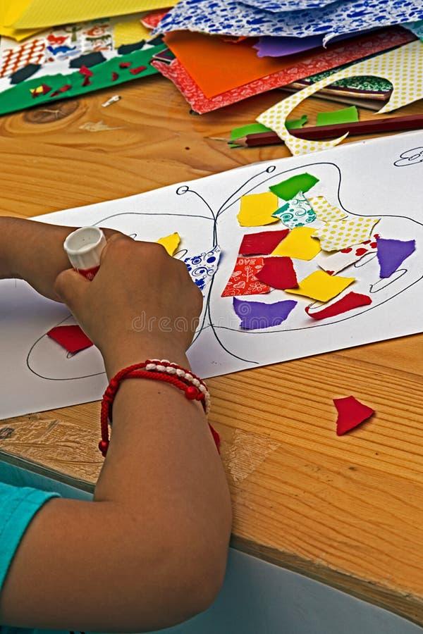 enfant qui colle ensemble des morceaux de papier color photo stock image 54909175. Black Bedroom Furniture Sets. Home Design Ideas