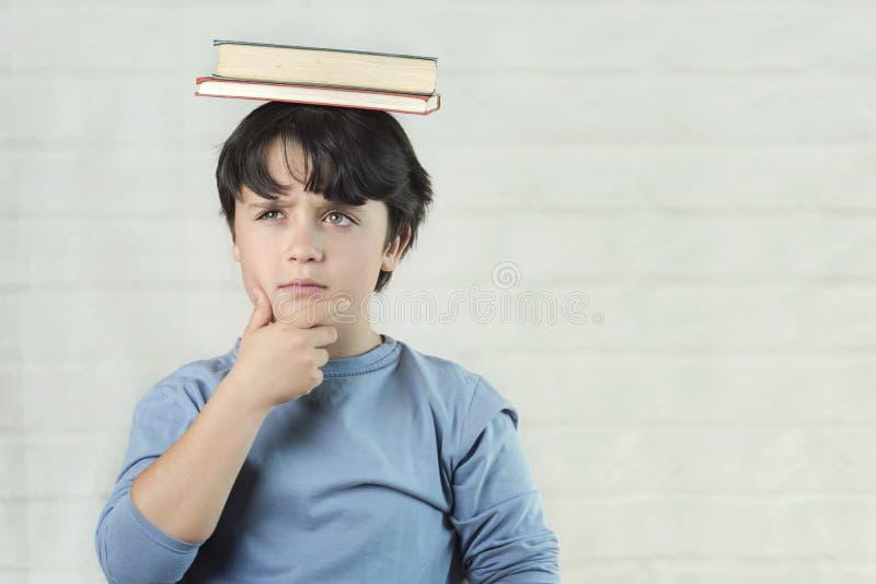 Enfant réfléchi avec des livres sur la tête photo stock