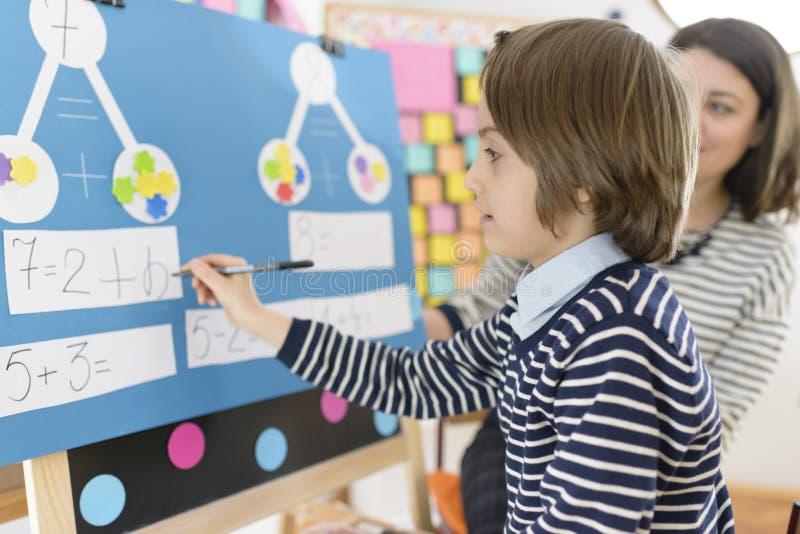 Enfant résolvant des exercices de maths images stock