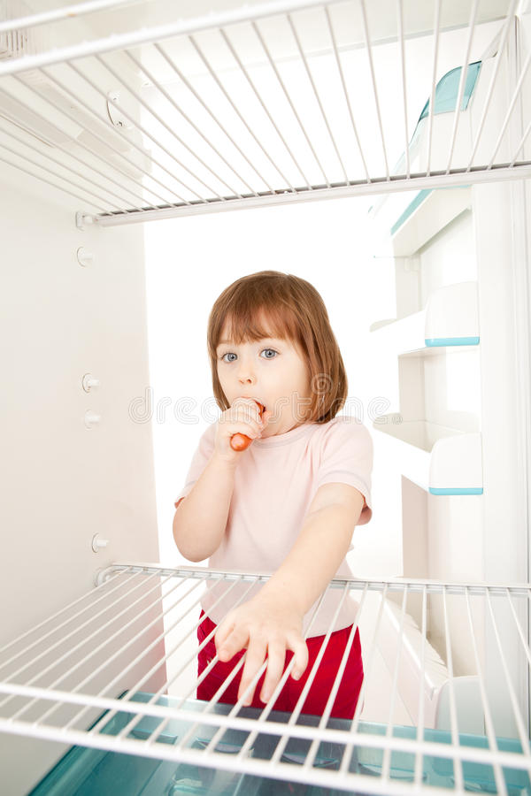 Enfant regardant dans le réfrigérateur vide photo stock