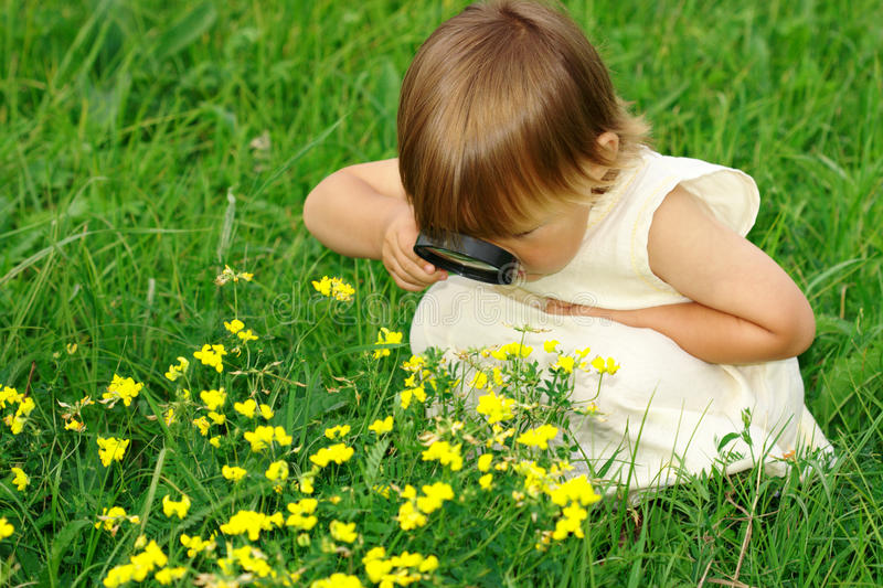 Enfant regardant des fleurs par la loupe images stock