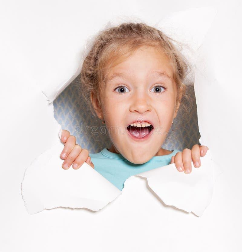 Enfant regardant hors d'un trou en papier image libre de droits