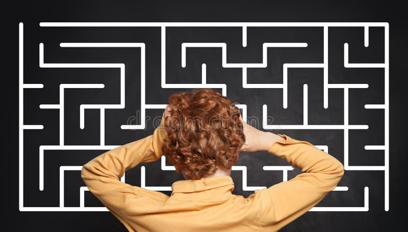 Enfant regardant le labyrinthe sur le fond de tableau photo stock