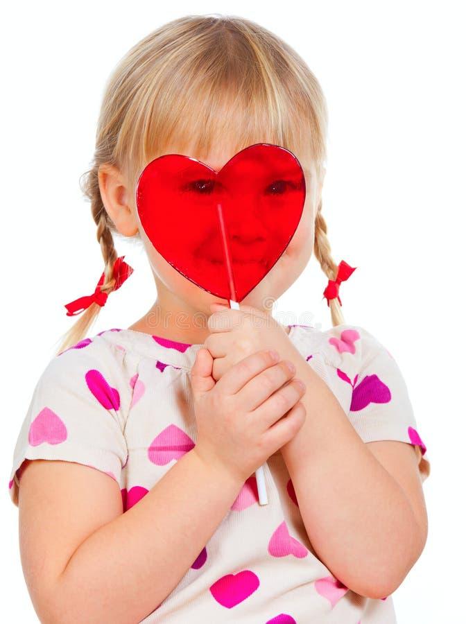Enfant regardant par le lollypop image stock